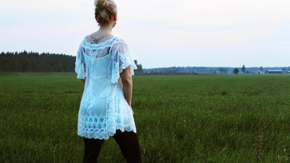 tyttö seisoo pellolla