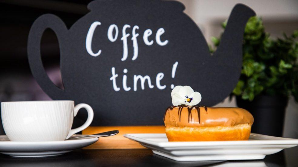 Kahvila junki kahvikuppi ja kuorrutettu pulla